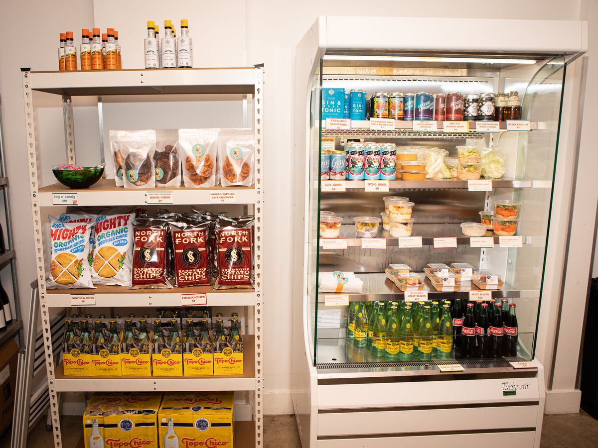 A white refrigerated case with beer, cold drinks, and some food on four shelves, and a white shelving unit stocked with chips, soda, and sauces