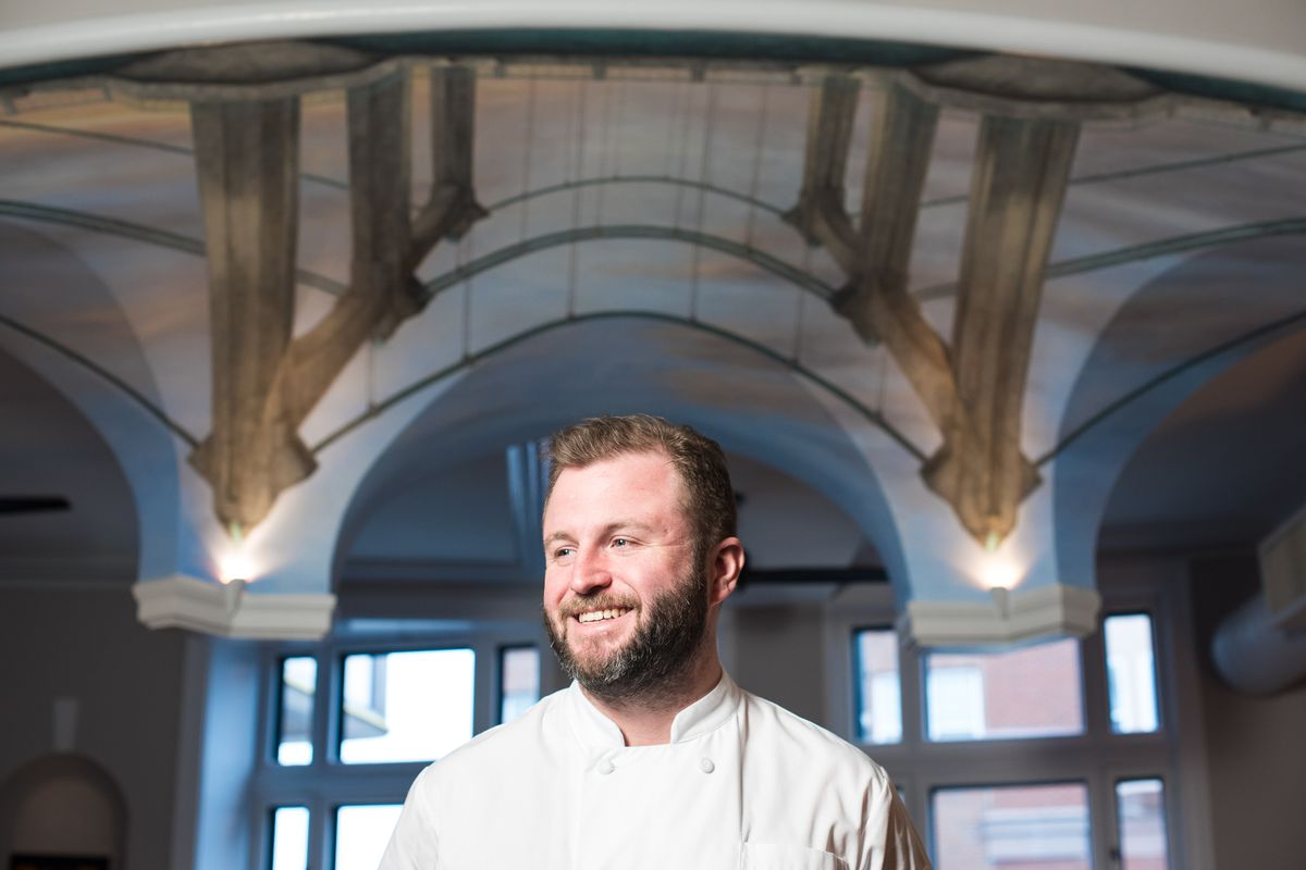 Chef Remy is smiling, behind him is an arch int he restaurant, painted with a mural of the Hennepin Avenue bridge