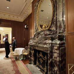 Two waiters confer near The Louis XVI fireplace of New York's St. Regis Hotel, Wednesday, March 14, 2012. A century after the Titanic sank, the legacy of the ship's wealthiest and most famous passenger, John Jacob Astor, quietly lives on at the luxury hotel he built in New York City.
