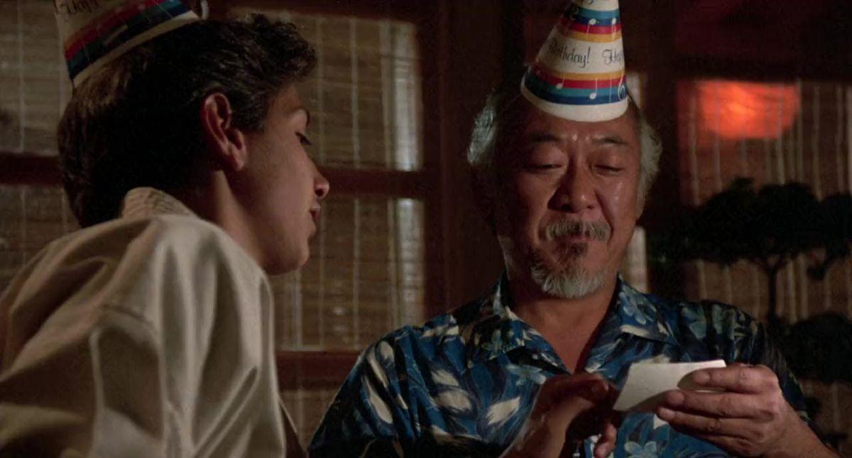 Mr. Miyagi (Pat Morita) reads a note from Daniel (Ralph Macchio)