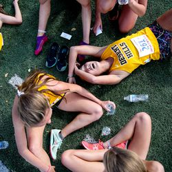 Desert Hills High School runners rest after the 4A girls cross-country state championship race at Highland High School in Salt Lake City on Wednesday, Oct. 23, 2019.