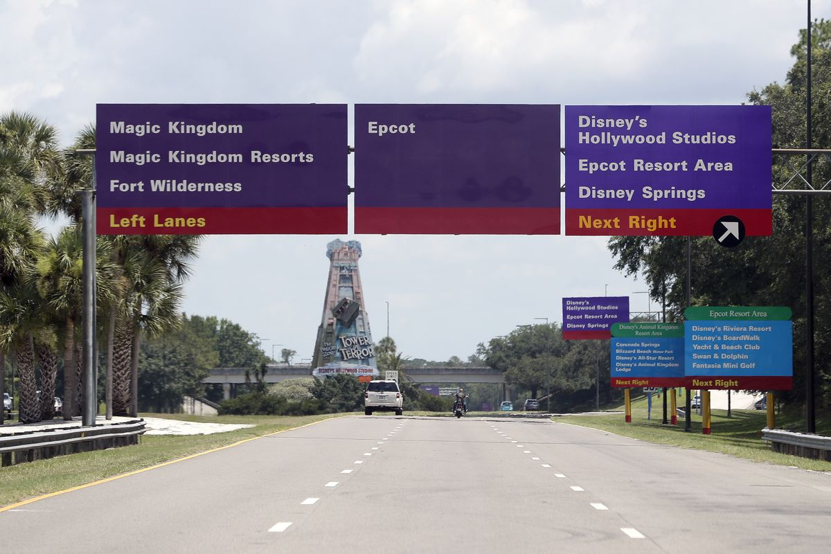 Signs direct motorists to the various theme parks at Walt Disney World, Thursday, July 2, 2020, in Lake Buena Vista, Fla.