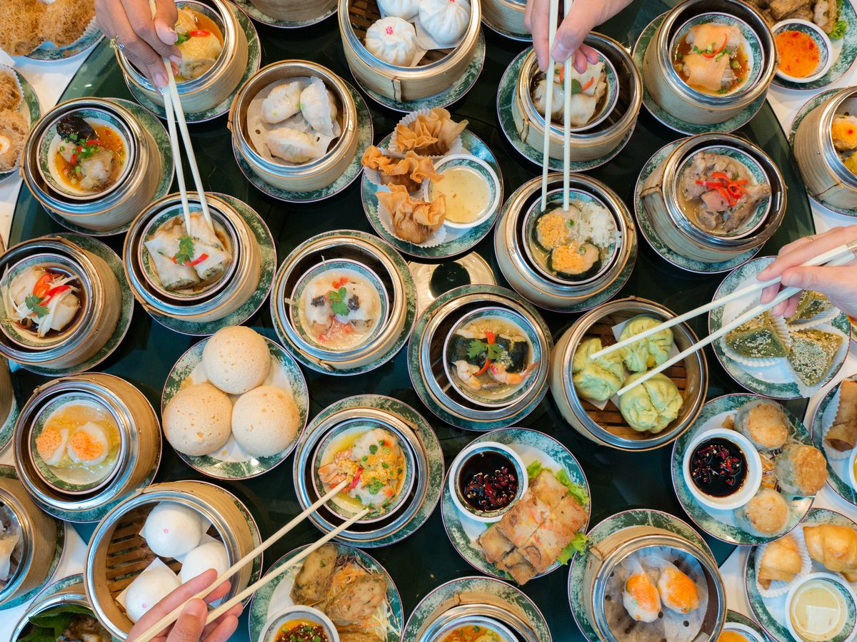 An overhead image of many dim sum dishes ranging from shrimp har gow to roast pork buns