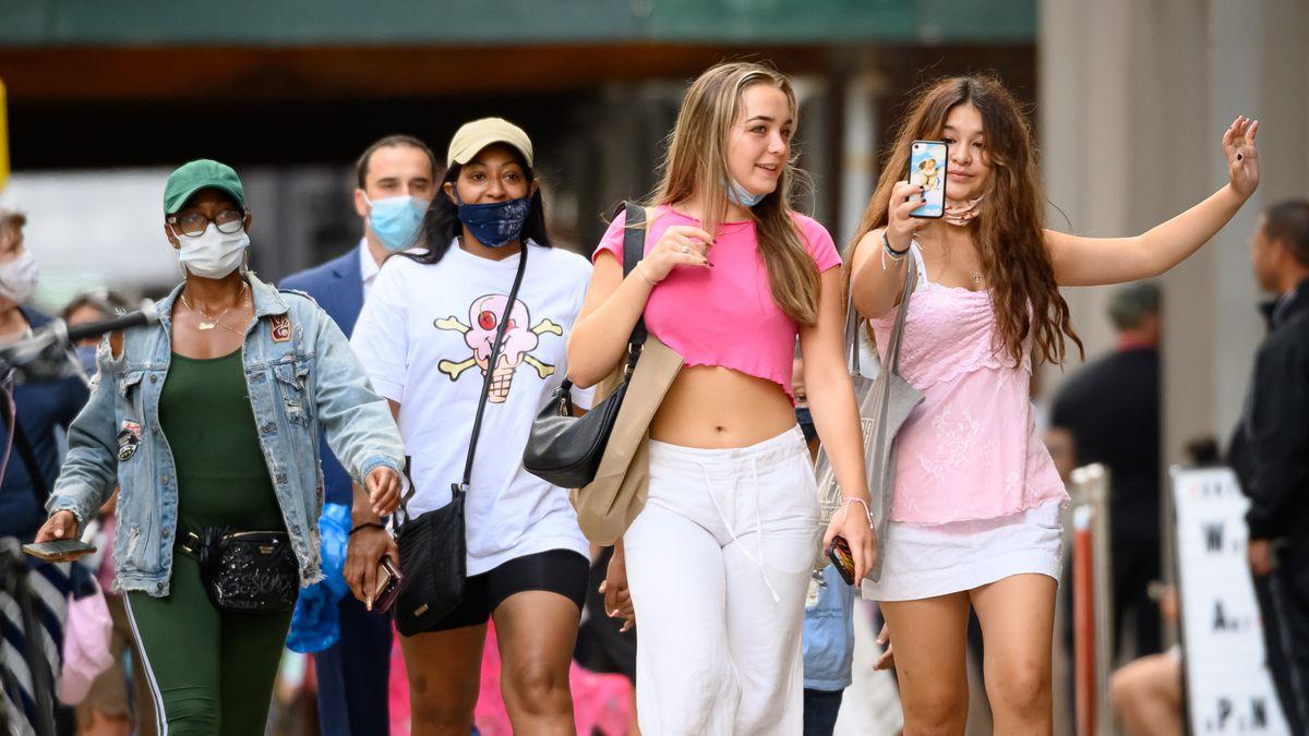Young women walking down a city street taking a selfie.