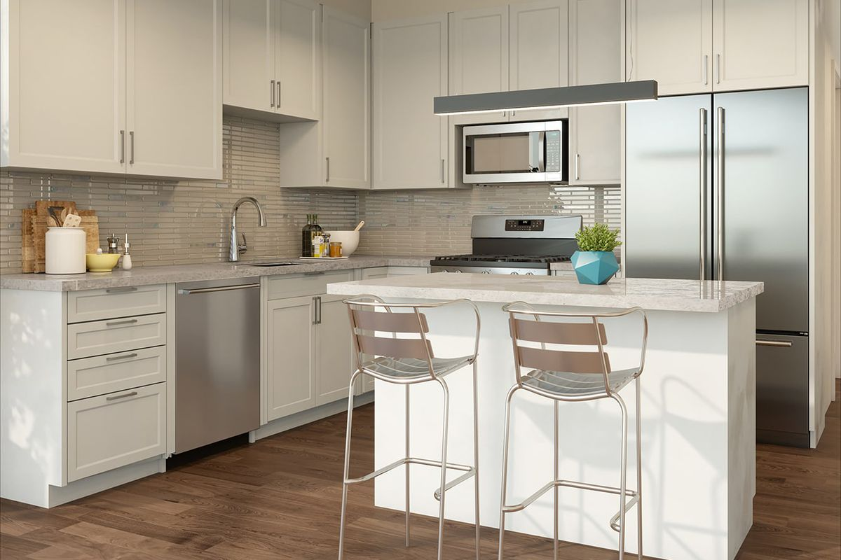 A new open kitchen with two stools in front of an island.