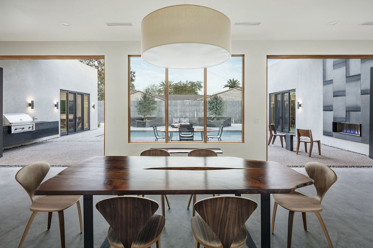 A dining area with a table, chairs, and tall windows overlooking a courtyard with a swimming pool.