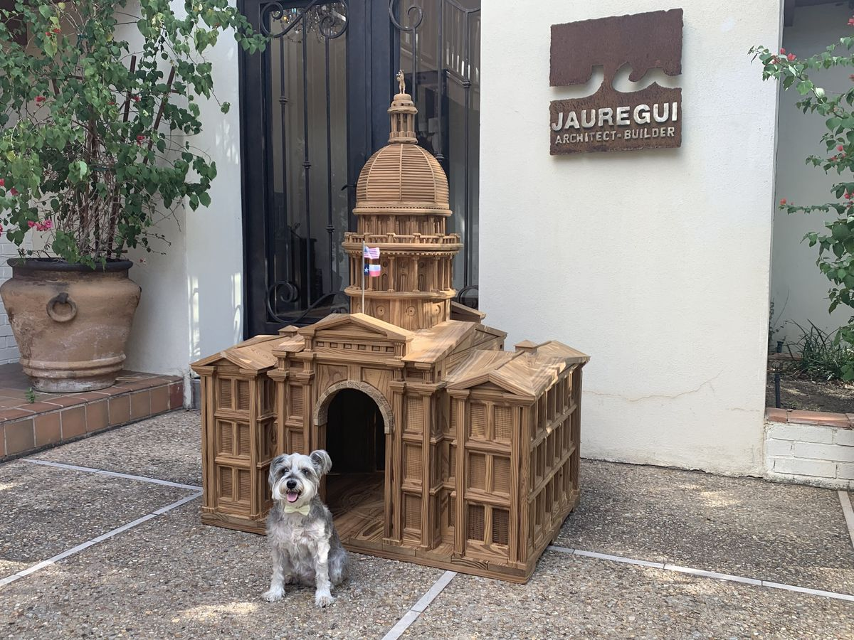 A small dog in front of a small replica of the Texas state capitol, a columned three-story building with an arched entrance and a tall cupola on top.