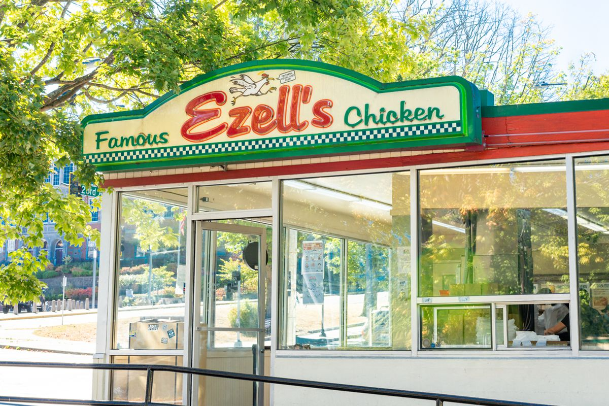 The exterior of Ezell's Famous Chicken restaurant, with glass windows, and a sign with green and red lettering and a cartoon chicken.