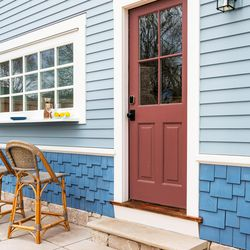 A four-color paint treatment accentuates the carpentry crew's careful craftsmanship. The red doors reference the color of the decorative rosettes in the gable ends' exterior trim. <em>Doors: </em><a class=