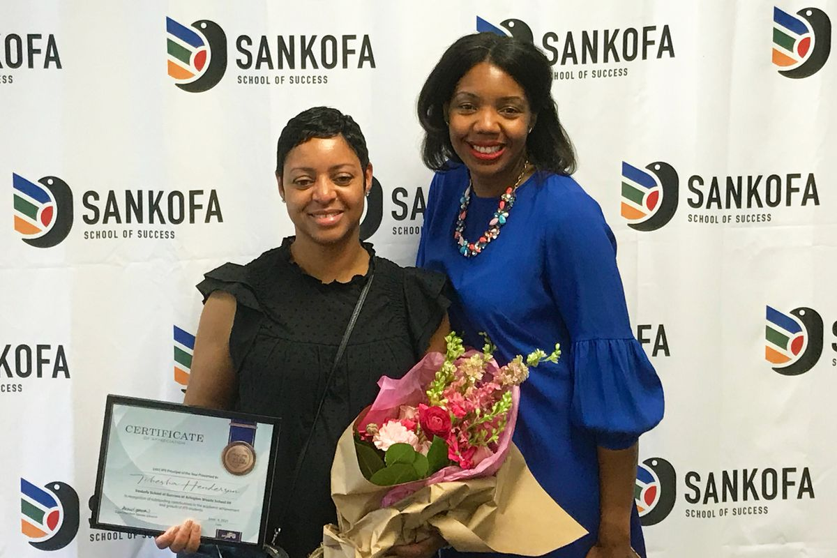 Two women embrace. One is carrying an award and a bouquet of flowers.
