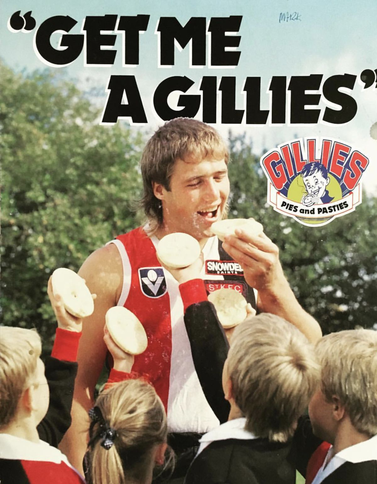 Tony Lockett eats a Gilles pie in front of a crowd of young fans