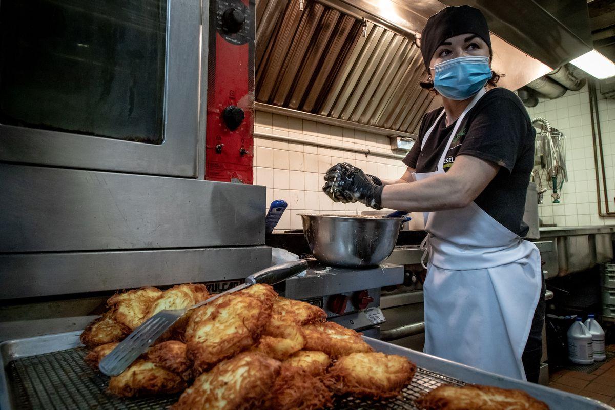 Nataliya fries up giant golden latkes while wearing a blue face mask