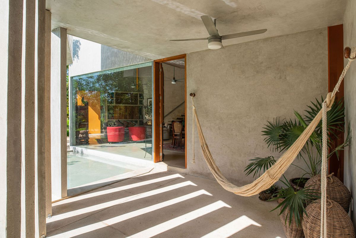 A covered area near the living room has a hammock and and plants in rattan baskets.