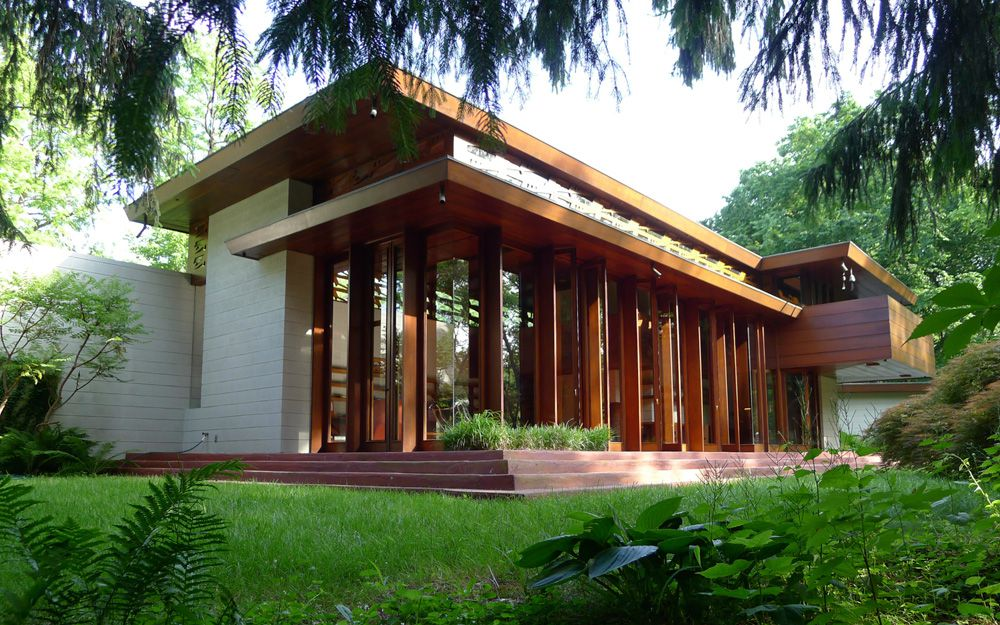 The Bachman-Wilson House by Frank Lloyd Wright. The facade is white brick with brown wood decorative framing and detail. There are floor to ceiling windows. There is a green lawn in front of the house.
