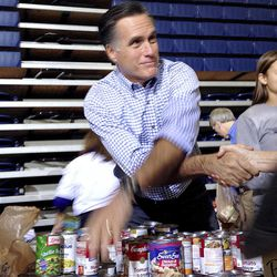 Republican presidential candidate and former Massachusetts Gov. Mitt Romney receives bags of food as he participates in a campaign event collecting supplies from residents local relief organizations for victims of superstorm Sandy at the James S. Trent Arena in Kettering, Ohio, Tuesday, Oct. 30, 2012. (AP Photo/Charles Dharapak)