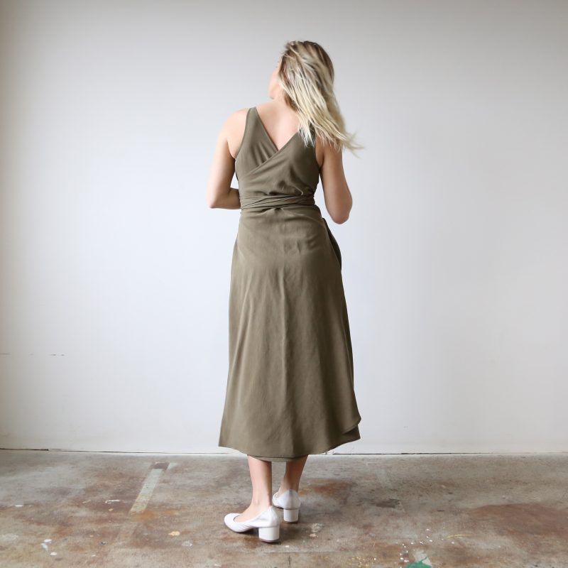 A model shows the back of a wrap dress in olive