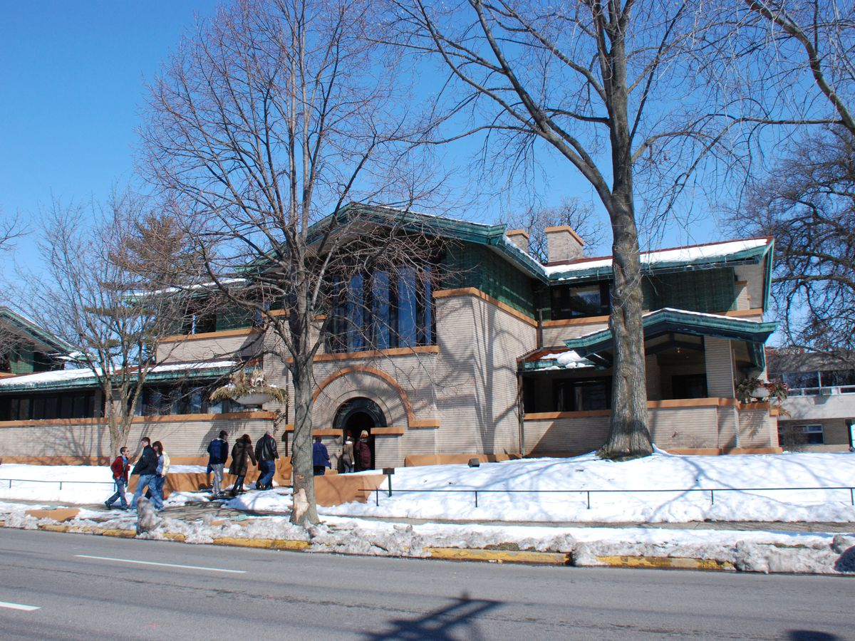 The Dana-Thomas House by Frank Lloyd Wright. The facade is tan with dark green and orange details. The house has multiple levels. There is a snow covered lawn in front of the house.