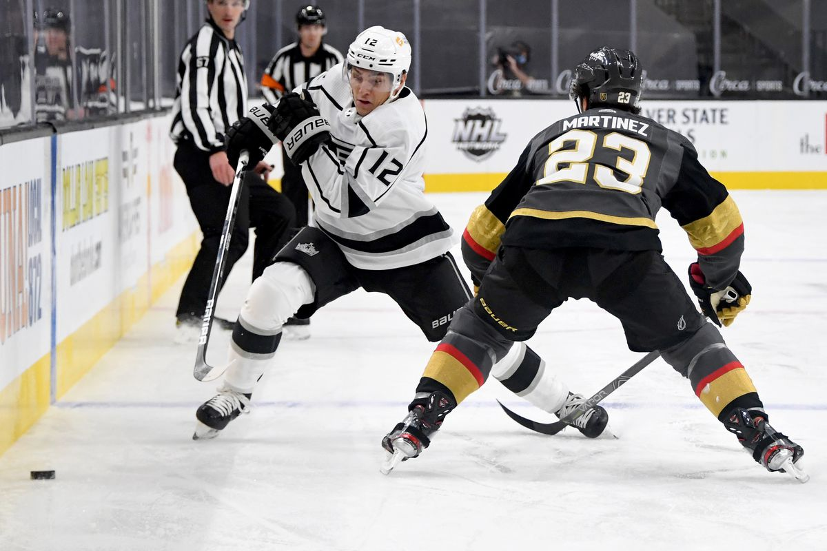 Trevor Moore #12 of the Los Angeles Kings tries to skate past Alec Martinez #23 of the Vegas Golden Knights in the first period of their game at T-Mobile Arena on February 5, 2021 in Las Vegas, Nevada. The Golden Knights defeated the Kings 5-2.