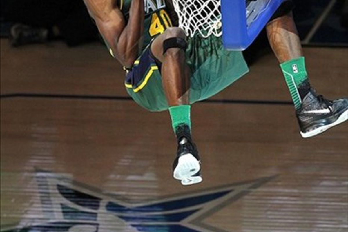February 25, 2012; Orlando FL, USA; Jeremy Evans of the Utah Jazz hangs on the rim after dunking two balls over teammate Gordon Hayward during the 2012 NBA All-Star Slam Dunk Contest at the Amway Center. Mandatory Credit: Kim Klement-US PRESSWIRE