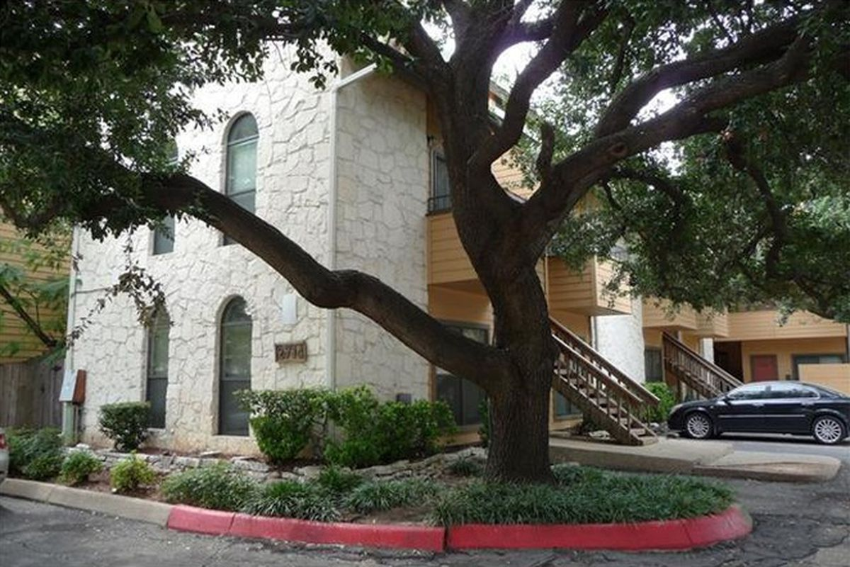 Exterior two-story white stucco apartment/condo building with big oak tree in front