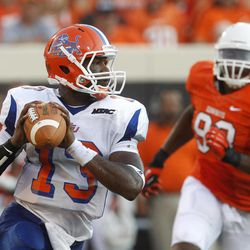 Savannah State quarterback Antonio Bostick (13) scrambles under pressure from Oklahoma State defensive tackle Davidell Collins (98) in the second quarter of an NCAA college football game in Stillwater, Okla., Saturday, Sept. 1, 2012.