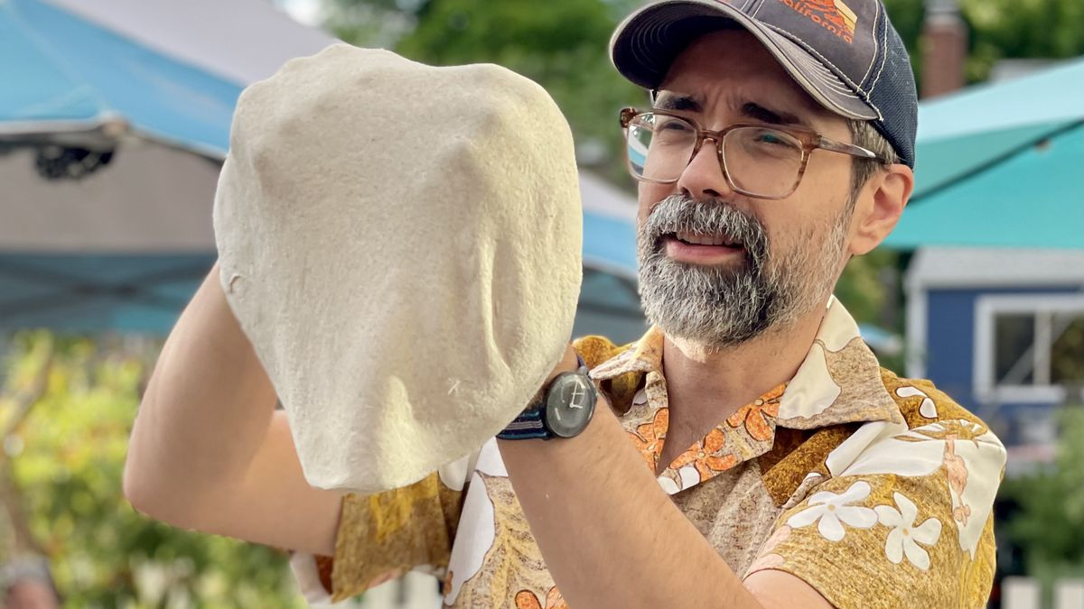 A man holds pizza dough over his knuckles in a loose, thin sheet in a Portland, Oregon backyard.