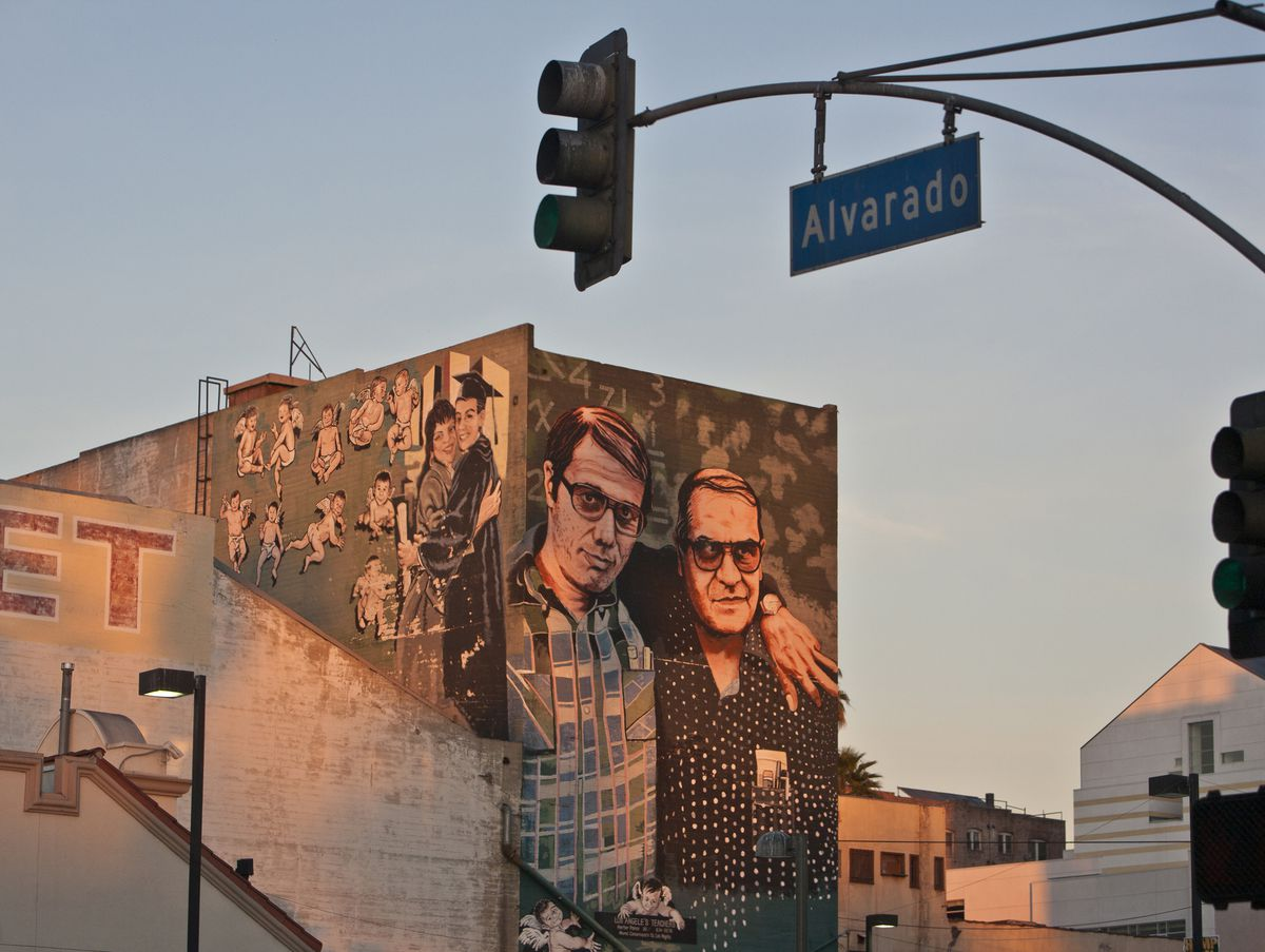 """A painting of actor Edward James Olmos and teacher Hymie Escalante (from the movie """"Stand and Deliver"""") is painted on the side of a building. A blue """"Alvarado"""" street sign and traffic signal in the foreground."""