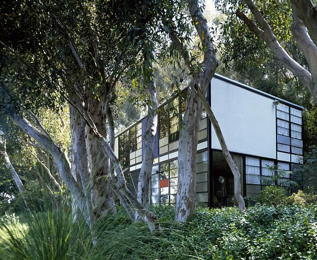 The exterior of the Eames House in California. The facade is white with colorful glass panels. The house is surrounded by trees.