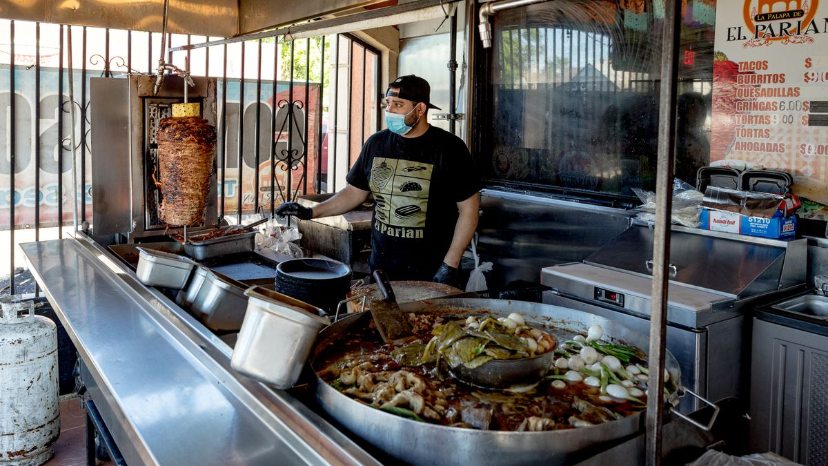 A man stands in a semi-enclosed patio space behind a table with a trompo on top and a large pot filled with stewed meat.