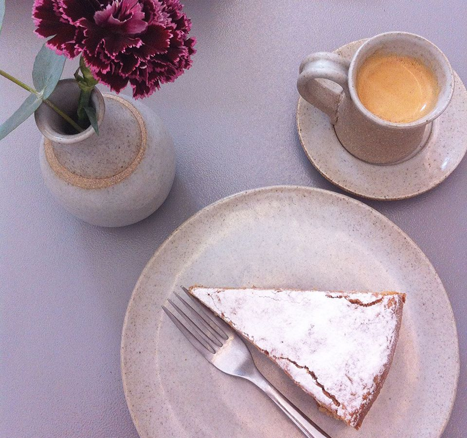 As seen from above, a slice of pie with a powdered topping sits on a plate with a fork, a cup of coffee and a flower in a small pot sit nearby.