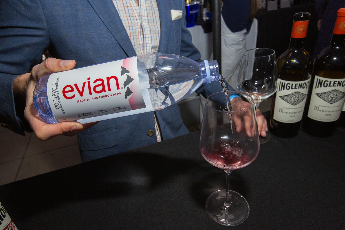 a wine rep washes out a glass with Evian water