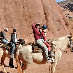 This undated image provided by the Navajo Tourism Department shows visitors riding horseback at Monument Valley Navajo Tribal Park in northeastern Arizona. An economic impact study and yearlong survey show spending by tourists on the Navajo Nation has increased by nearly one-third since 2002. (AP Photo/Navajo Tourism Department, Roberta John)