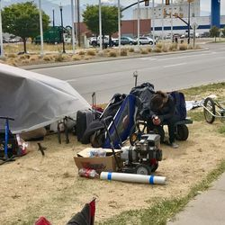 """Tawnee sits by her shelter along 500 West with her possessions in a blanket-covered wagon in Salt Lake City on Monday, Aug. 14, 2017. Tawnee, who said she has been addicted to drugs """"a long time,"""" was later arrested on 13 outstanding warrants during Operation Rio Grande."""