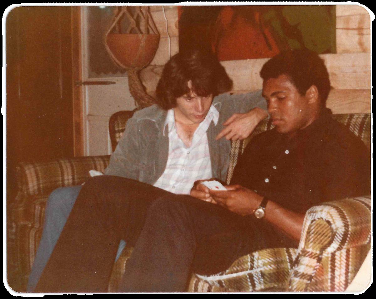 Terry La Sorda and Muhammad Ali practice card tricks.