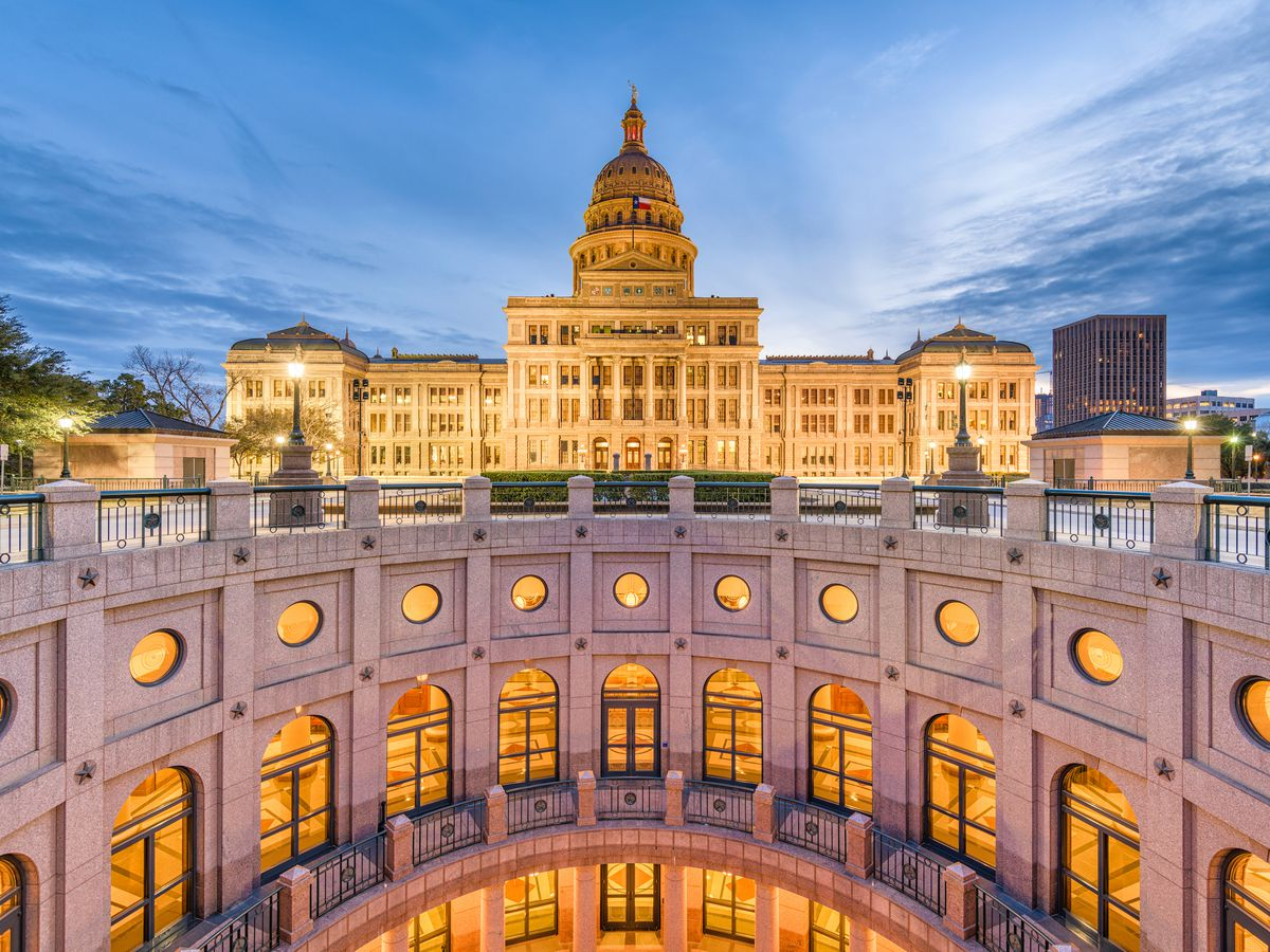 The exterior of the Texas State Capitol Building. The facade is pink granite. In the distance is a building with a dome structure on top.