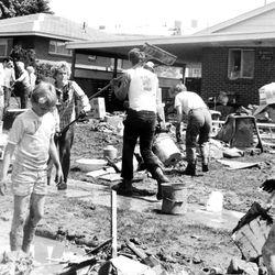 Neighbors, friends, and strangers join in one of countless team efforts to help clean up the yard of Willard Johansen in Bountiful, Utah. June 4, 1983.