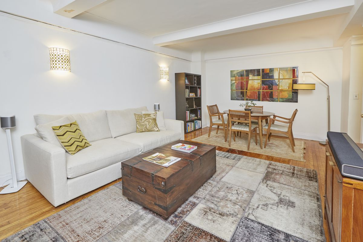 A living area with beamed ceilings, hardwood floors, a beige couch, and wooden furniture.