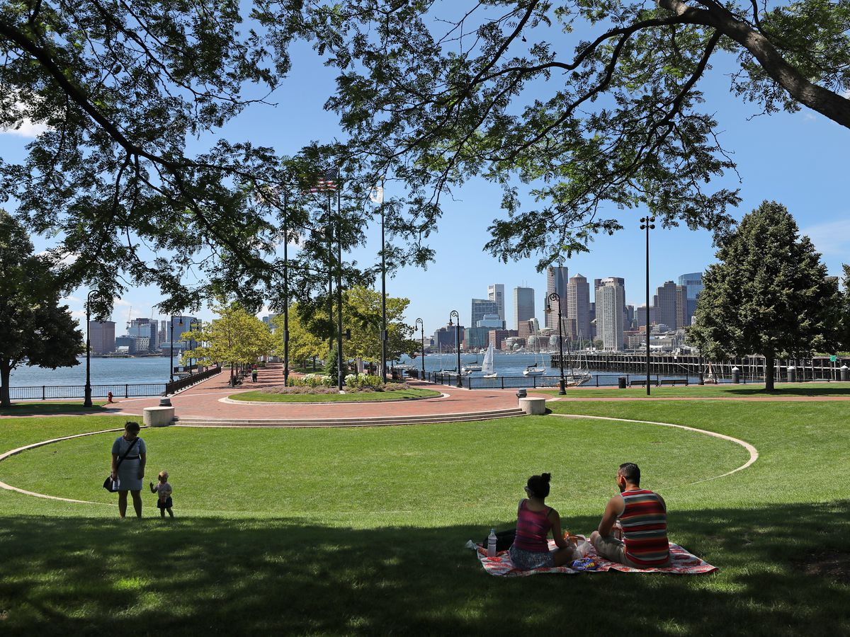 A waterfront park with a city skyline in the background, and there are people in the park.
