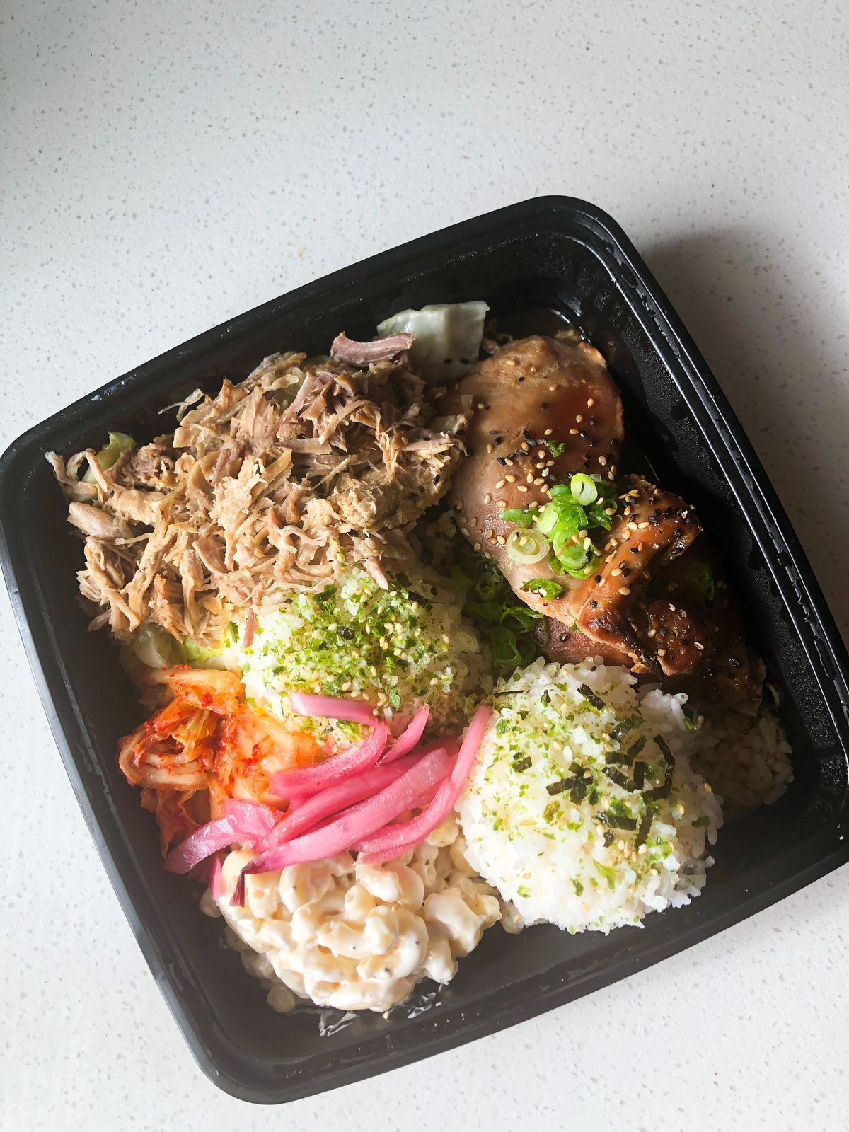 A takeout container of rice, mac salad, teriyaki-style chicken and kalua pig on a counter