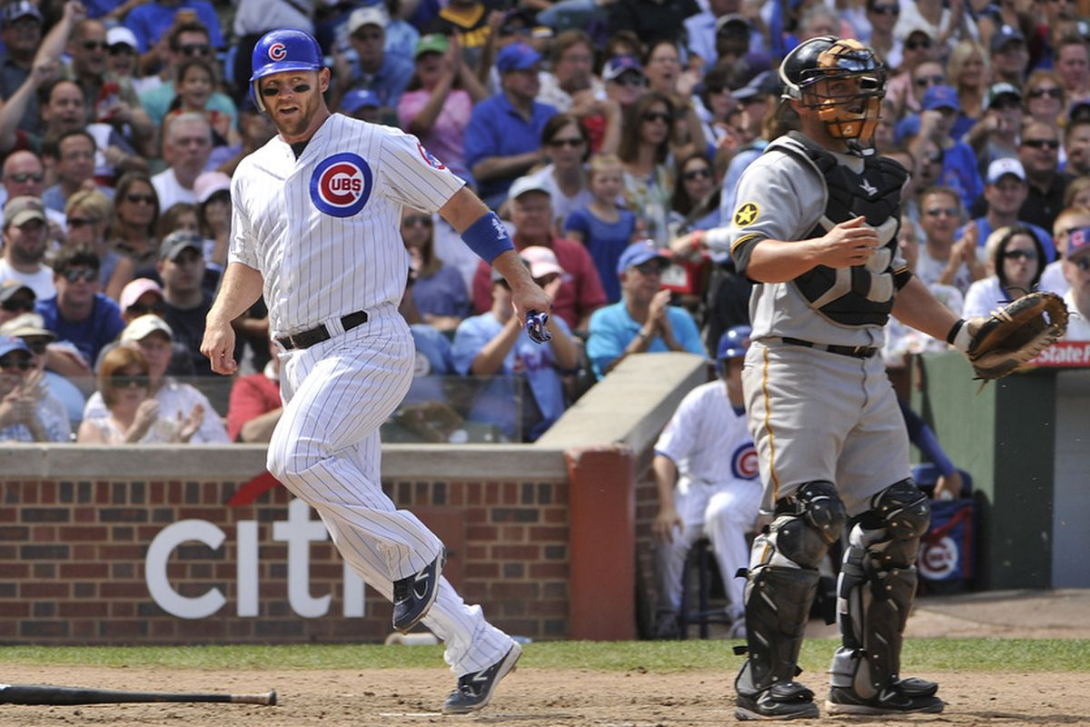 Koyie Hill of the Chicago Cubs scores past catcher Michael McKenry of the Pittsburgh Pirates after Starlin Castro hit an infield single at Wrigley Field in Chicago, Illinois.  (Photo by Brian Kersey/Getty Images)