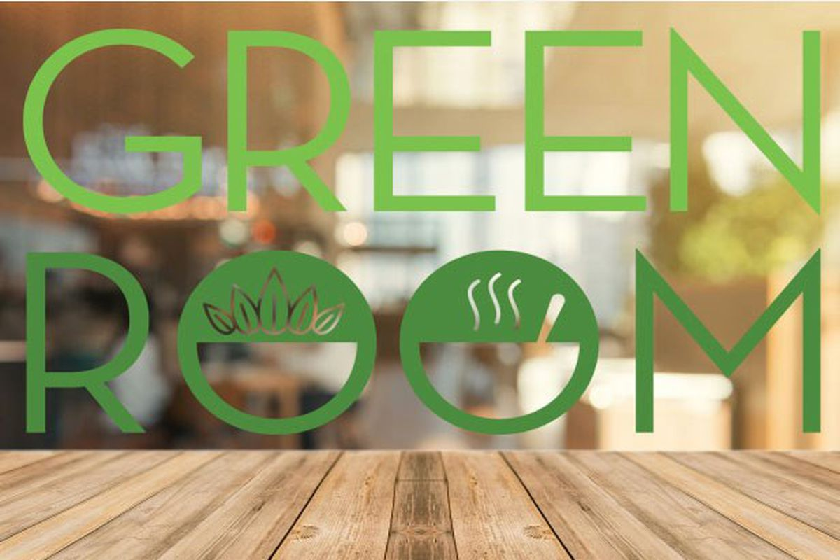 a green lettered sign for the green room on a window above a slatted wood table