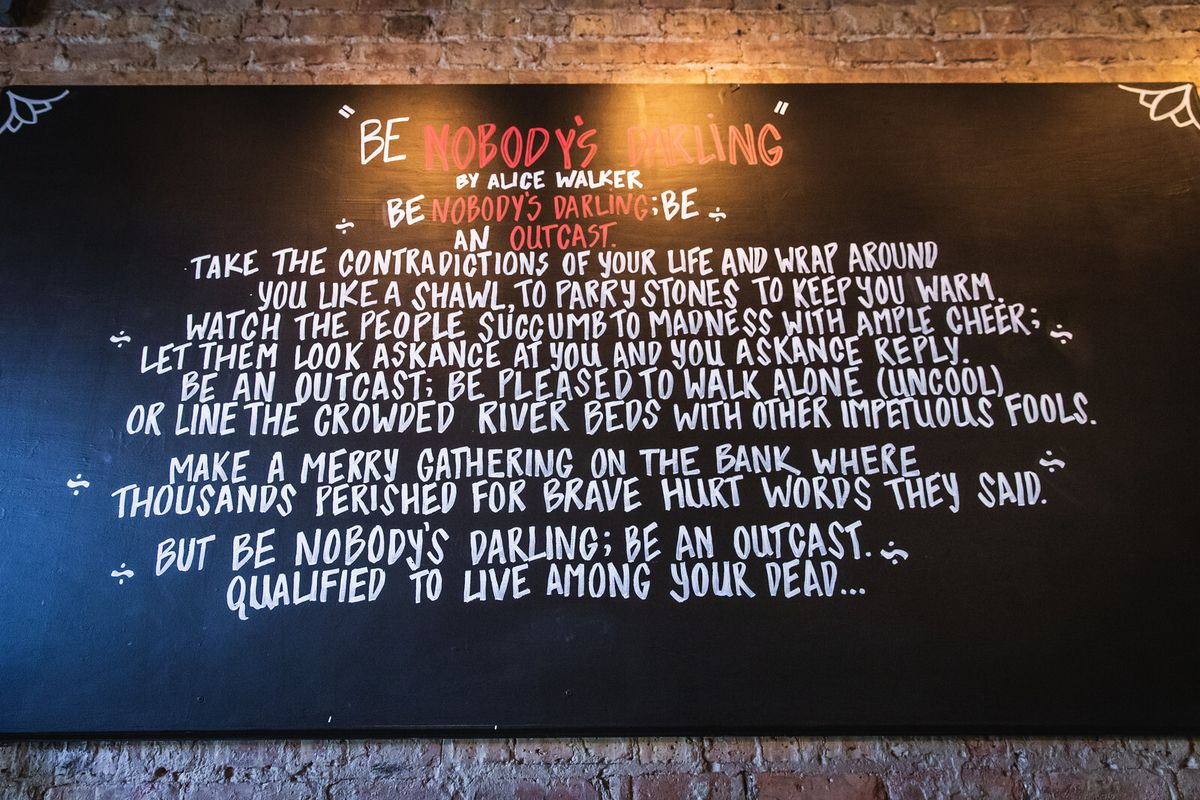 """A black board with the poem """"Be Nobody's Darling"""" by Alice Walker written in white letters"""
