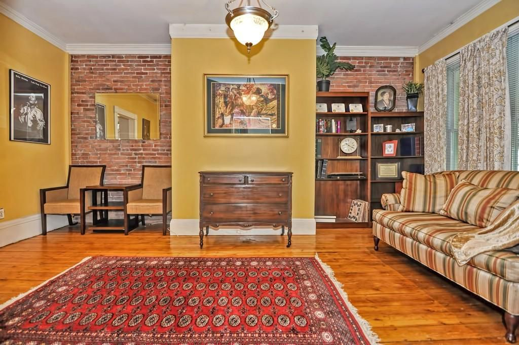 A living room with the furniture against the wall and a rug covering much of the area.
