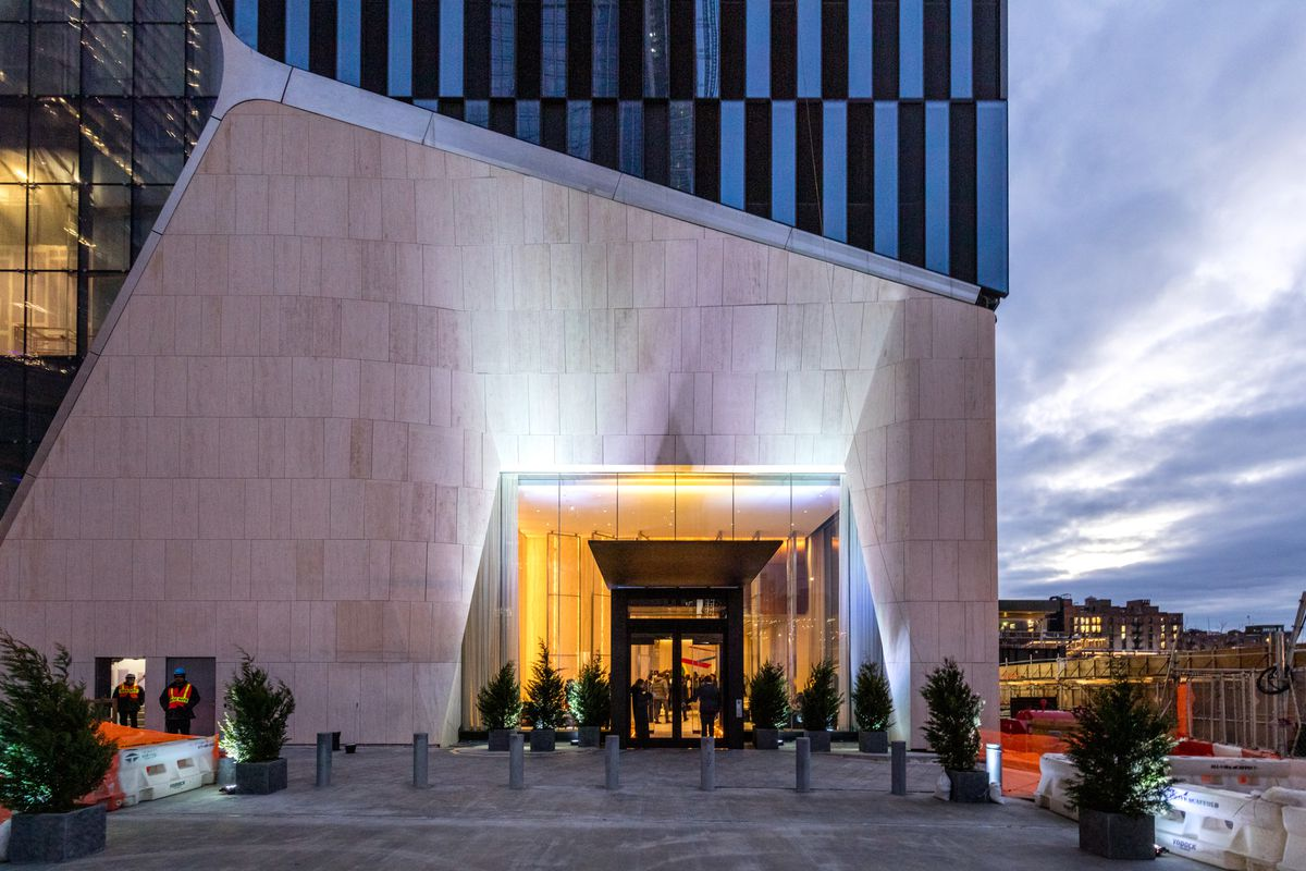 A building with a large entryway and a stone exterior. There are multiple plants in planters surrounding the entryway. The interior is lit with yellow light.