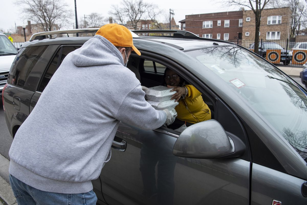 Darryl Tabernacki, father and spouse to faculty at Leo High School, gives food to a students parent outside Leo High School, Friday, April 24, 2020.