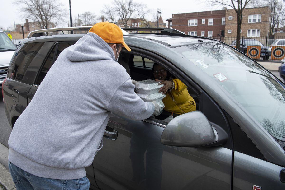 Darryl Tabernacki, père et conjoint de la faculté de Leo High School, donne de la nourriture à un parent d'élèves à l'extérieur de Leo High School, le vendredi 24 avril 2020.