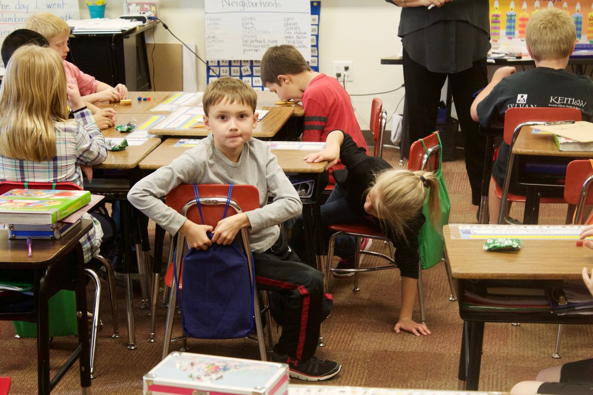 Elementary school students work begin work on an English assignment while enjoying a mid-morning snack.