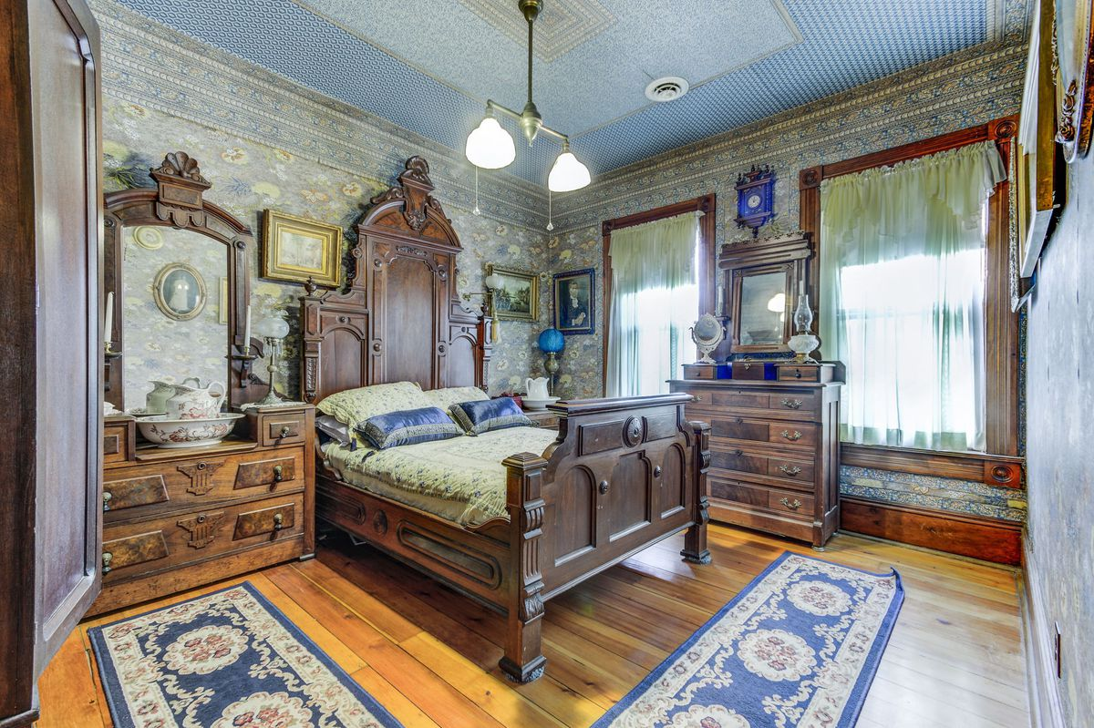 A bedroom features a large four poster wooden bed, wood floors, green wallpaper, and heavy Victorian styled wood furniture.