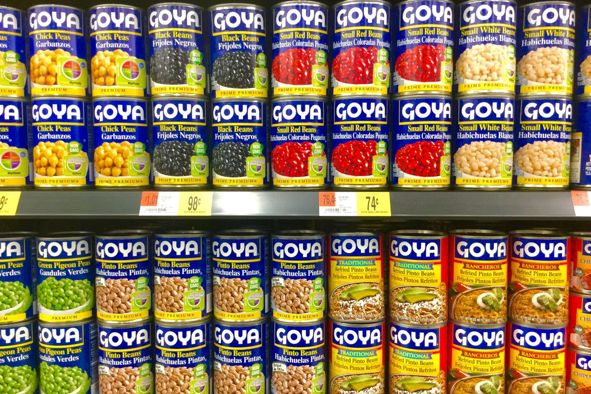 Cans of Goya beans stacked in a grocery aisle
