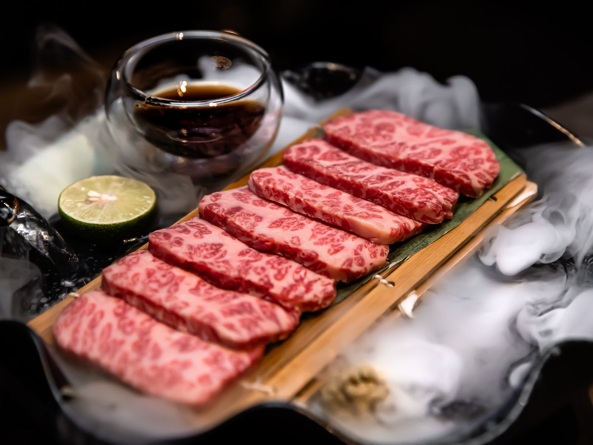 A tray of tender beef slices with a cut lime and sauce ramekin sit on top of an artful display against a black backdrop.